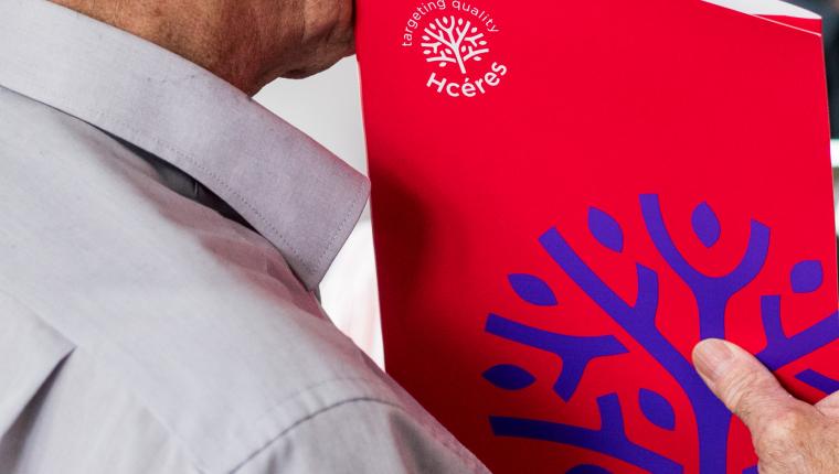 Homme tenant une pochette avec le logo Hcéres dessus