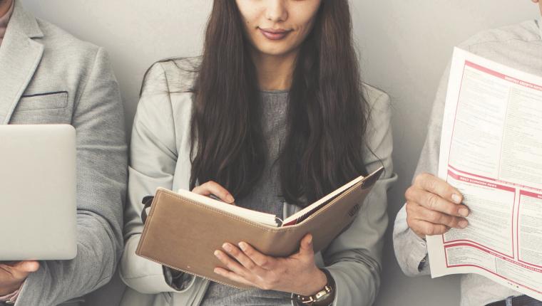 Personnes lisant des actualités dans un journal, des ordinateurs et smartphones.